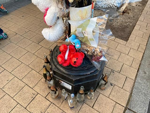 Vor einem Sozialbau die Überreste einer Abdankungsfeier: Bär, Blumen und Alkoholflaschen.