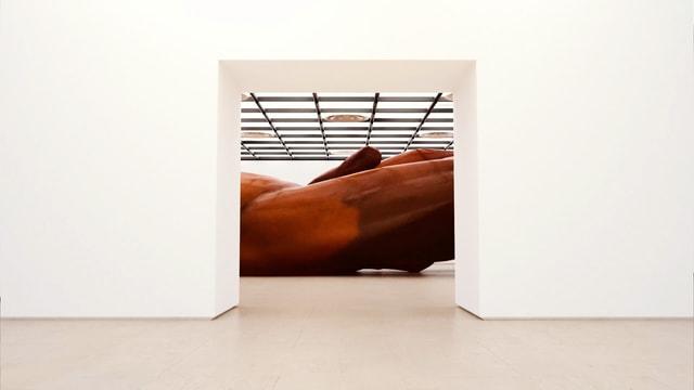 Weisser Raum. Durch eine Türe sieht man eine grosse Skulptur im Nebenraum.