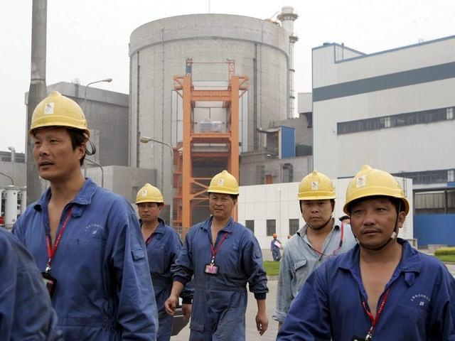 Fünf chinesische Atomarbeiter mit blauen Overalls und gelben Helmen vor einem Atomkraftwerk