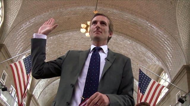 Michiel Vos hebt seine rechte Hand zum Treueschwur. Zwei US-Flaggen hängen seitlich an der Wand.