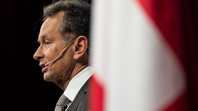 FDP-Parteipräsident Müller von der Seite hinter einer Schweizer Fahne und mit einem Mikrophon an der Backe.
