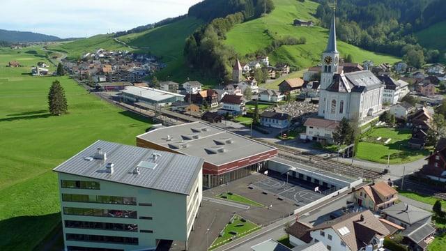 Ein Dorf mit einem Schulhaus im Vordergrund, rechts eine Kirche und links eine grosse Wiese.