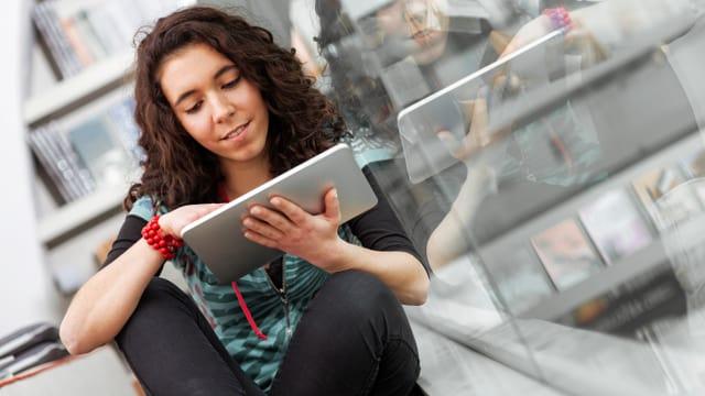 Eine Frau sitzt in einer Buchhandlung und liest ein Ebook.