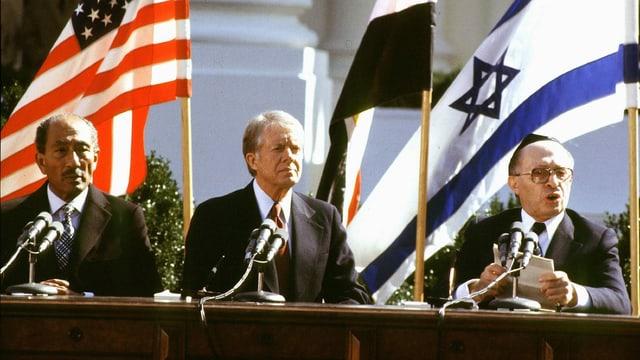 Die drei Politiker sitzen vor Landesflaggen.