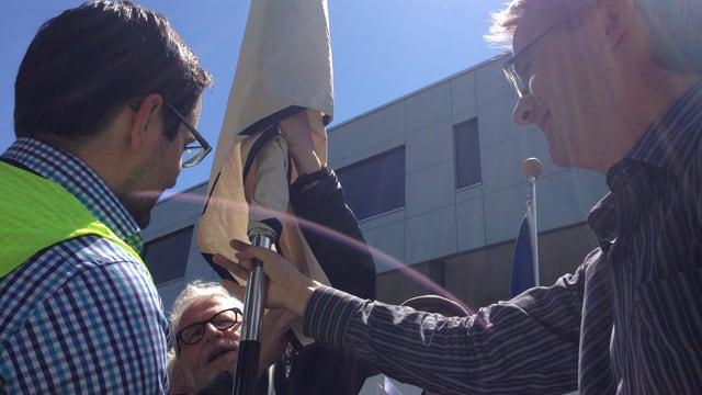 Drei Männer entfachen eine Fahne, sie scheinen damit Mühe zu haben.