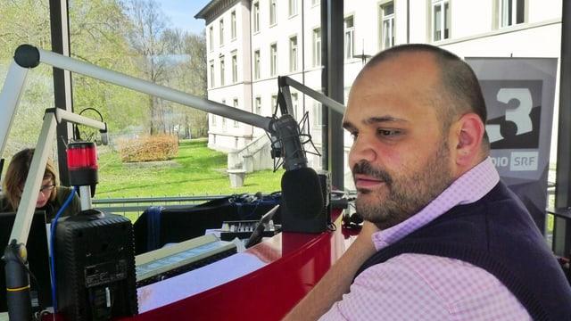 Zu sehen ist ein Mann vor einem Mikrophon. Im Hintergrund ein Gebäude der Klinik Waldhaus in Chur.