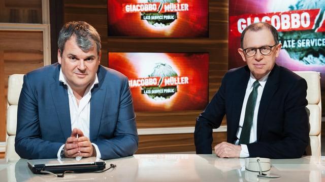 Mike Müller und Viktor Giacobbo sitzen am Pult.