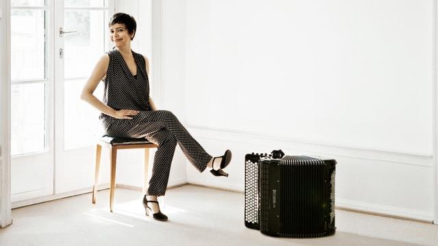 Chassot sitzt auf einem Stuhl in einem leeren, weissen Raum. Ein Akkordeon steht auf dem Boden neben ihr.