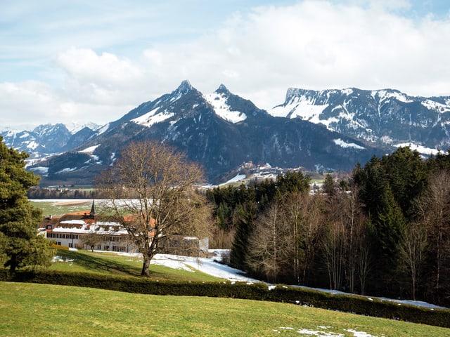 Landschaft vor Bergen mit Kloster.