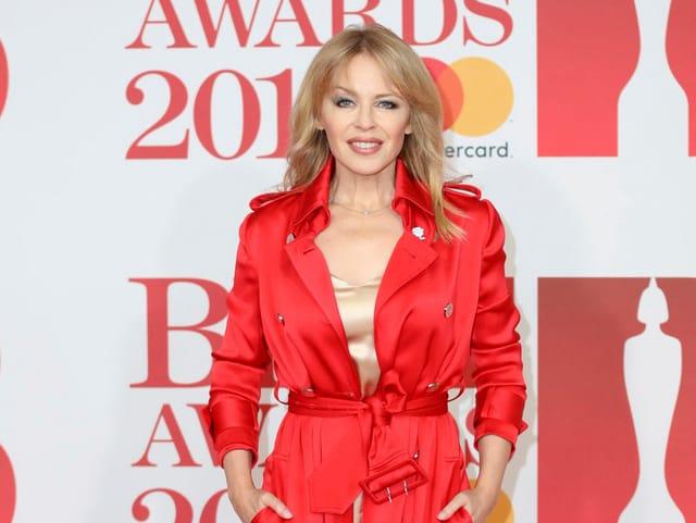 Kylie Minogue mit rotem Tranchoat vor einer Fotowand.