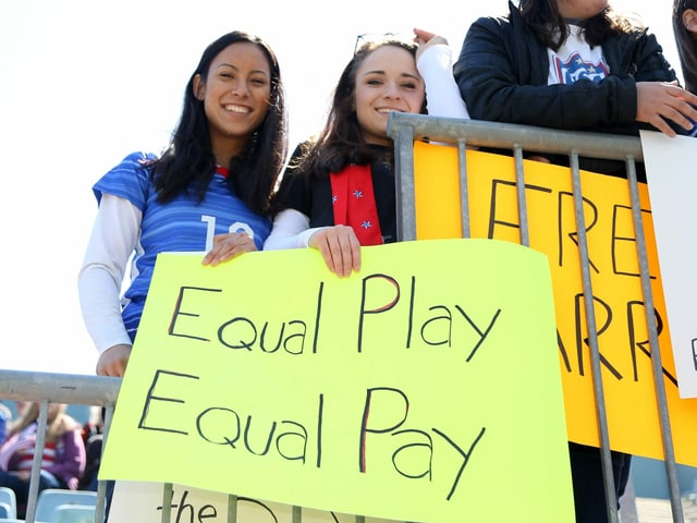 Zwei Frauen halten ein Plakat in die Höhe.