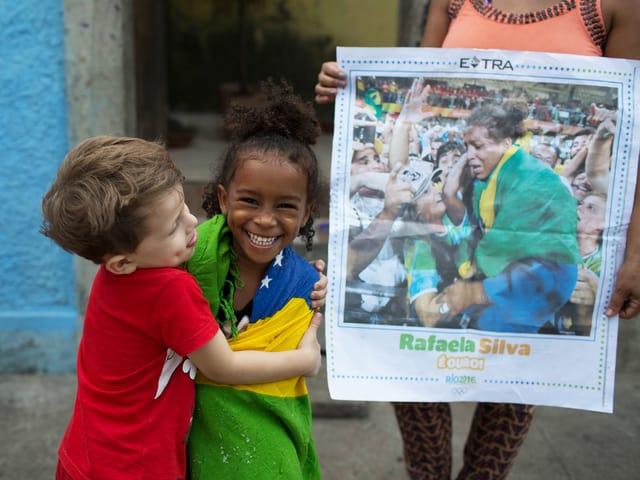 Rafaelas vierjährige Cousine Giovana Silva wird von einem Nachbarsjungen umarmt, daneben hält eine Frau einen Zeitungsartikel mit dem Bild der Siegerin.