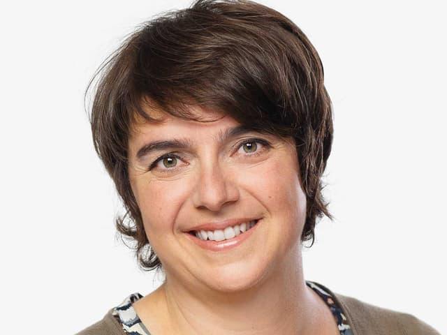 Porträt einer dunkelhaarigen Frau mit braun-grünen Augen.