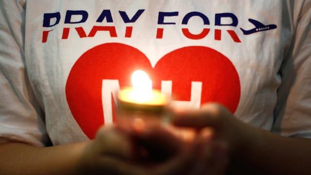 Ein Mensch hält eine Kerze vor der Brust. Im Hintergrund das T-Shirt mit der Aufschrift: Pray for MH370.