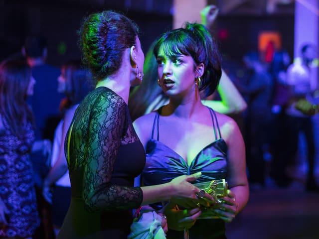Zwei junge Tunesierinnen sprechen in einer Disco miteinander.