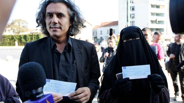 Rachid Nekkaz und Frau in Niqab mit Schecks in den Händen