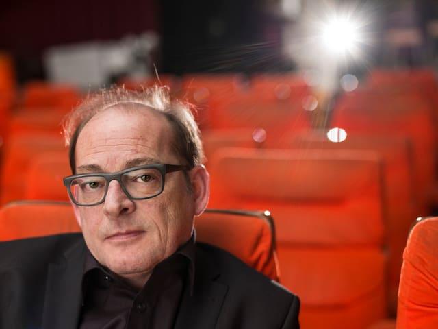 Ivo Kummer sitzt in einem Kino, blickt in die Kamera während hinter ihm der Projektor läuft.