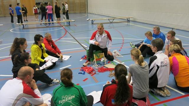 Hansjörg Thommen sitzt am Boden einer Turnhalle. Um ihn herum eine Gruppe Junger Kursteilnehmerinnen und Teilnehmer.