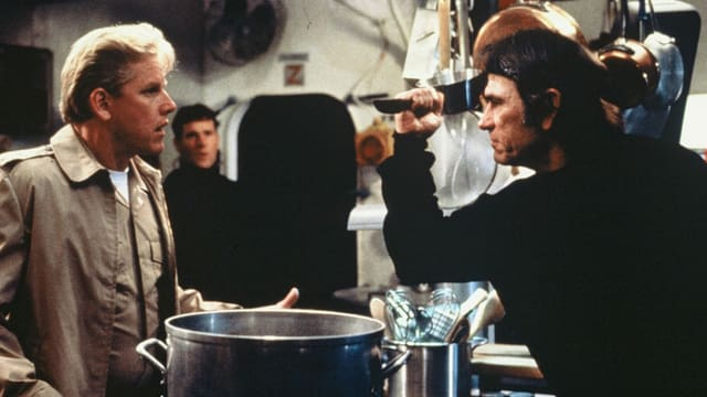 Zwei Männer stehen sich gegenüber. Zwischen ihnen befindet sich ein Kochherd. Der Mann auf der rechten Seite hält ein Messer in der Hand.
