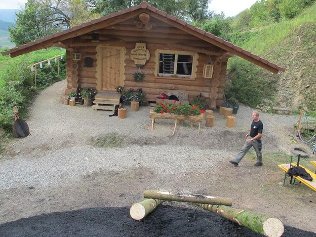 Holzhütte im Hintergrund, Kohleberg im Vordergrund, Mann läuft durch das Bild.