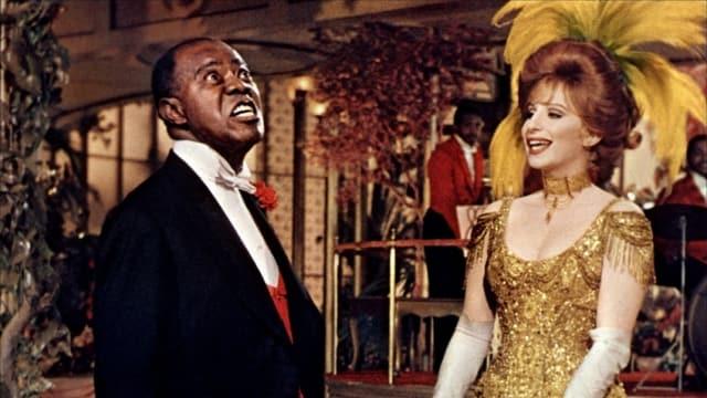 Dolly trägt goldenes Kleid und gelben Federhut. Louis im Frack. Die beiden begegnen sich im luxuriösen Speiselokal. Es handelt sich um die Szene, bei der das Titellied «Hello, Dolly!» erklingt.