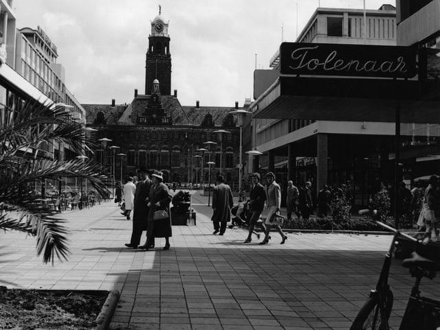 Eine Einkaufstrasse in Rotterdam aus den 50er-Jahren. Ein paar Menschen sind im Bild.