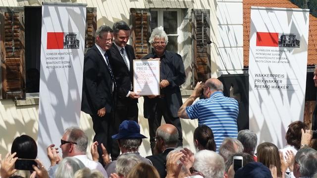 Martin Killias il parsura da la protecziun da la patria svizra (sanester) surdat il premi a l'intendant da Origen Giovanni Netzer (entamez) ed a Andrea Hämmerle, il president da la Pro Origen.