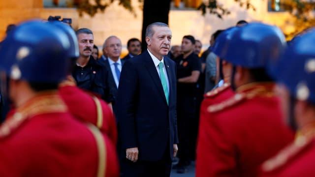 Der türkische Präsident Erdogan steht vor Soldaten.
