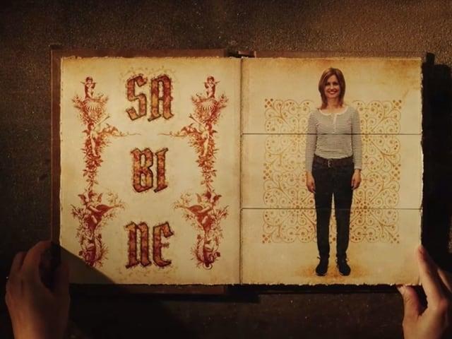 """Bilderbuch, auf der linken Seite ist in alter Schrift der Name """"Sabine"""" zu lesen, rechts steht eine Frau in modernen Kleidern"""