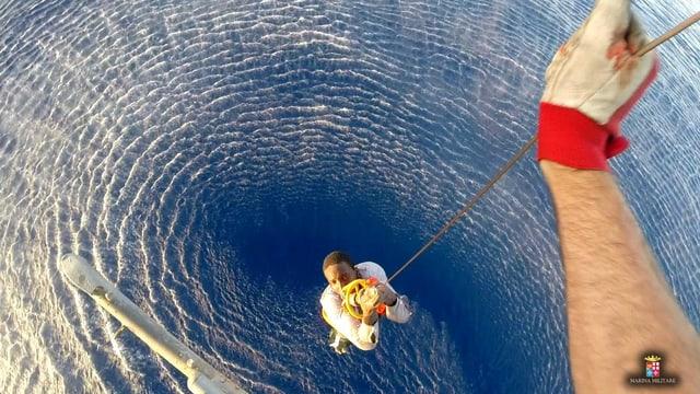 Ein dunkelhäutiger Mann wird mit einer Seilwinde aus einem blauen Ozean in einen Helikopter gehievt. Das Bild wurde aus dem Helikopter geschossen, man sieht nur eine Hand, das Seil und weiter unten ein Mann, der daran hängt und nach oben in die Kamera blickt. Unter ihm das blaue Meer.