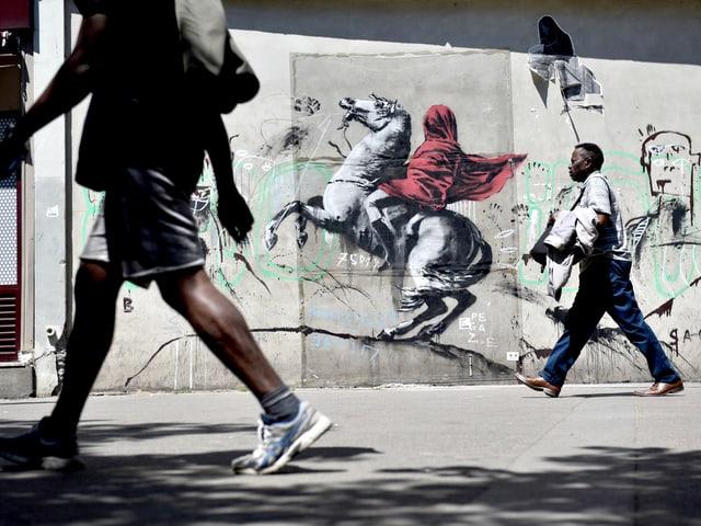 Schablonenkunst auf einer Fassade: Das Kunstwerk zeigt einen Reiter mit einem roten Umhang.