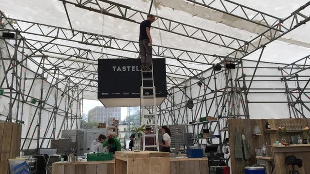 Ein Mann steht auf einer Leiter und befestigt etwas an einem Querbalken. Hinter der Leiter ist ein Schild mit der Aufschrift «Tastelab».