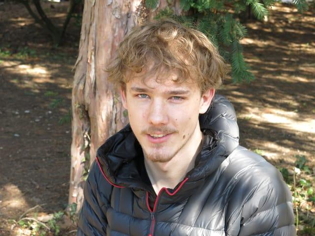 Junger Mann mit blonden Haaren und blauen Augen steht im Wald.