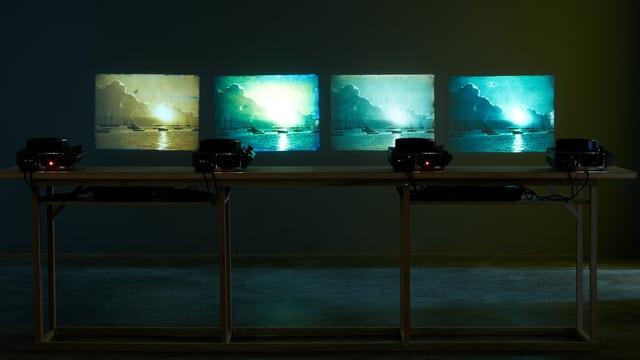 Das Bild zeigt an eine Wand projizierte Dia-Bilder von Sonnenuntergängen in blauer Farbe.