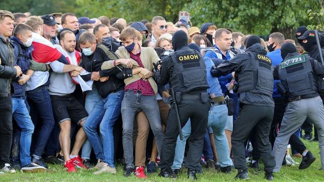 Demonstranten werden von Sicherheitskräften zurückgehalten.