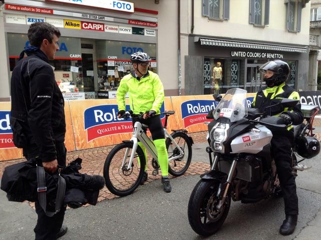 Drei Männer, einer steht, einer sitzt auf einem E-Bike, einer sitzt auf einem grossen Motorrad.
