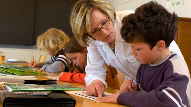 Eine Lehrerin erklärt einem Schüler eine Aufgabe.