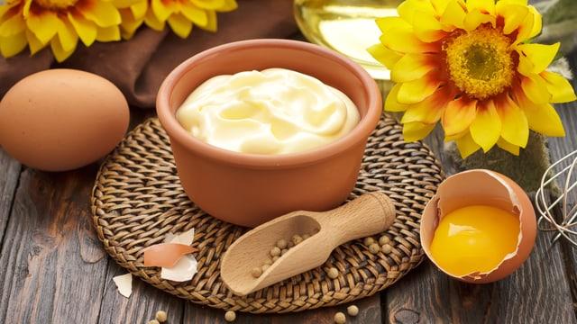 Mayonnaise mit Ei, Pfeffer und Ölfläschchen im Hintergrund.