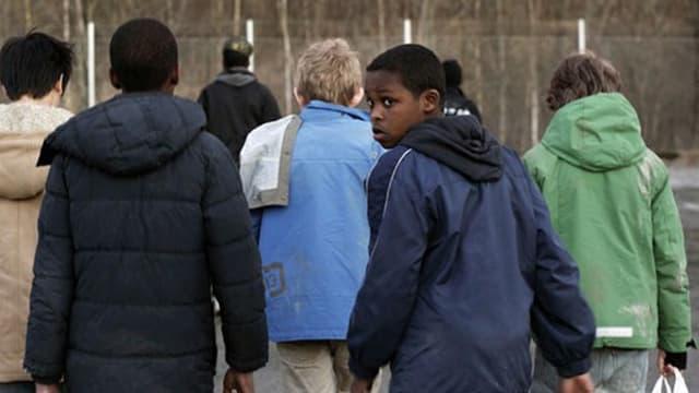 Ansicht von hinten: eine Gruppe von Jungen geht weg, einer guckt in die Kamera.