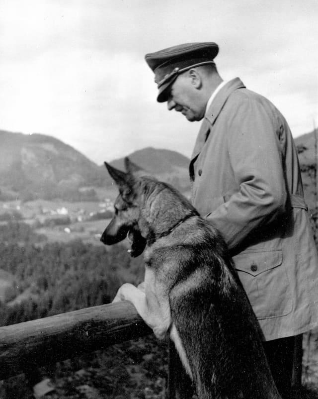 Hitler und sein Schäferhund lehnen an ein Holzgeländer und schauen in die Ferne.