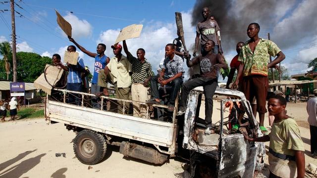 Männer stehen auf einem ausgebrannten Autowrack.