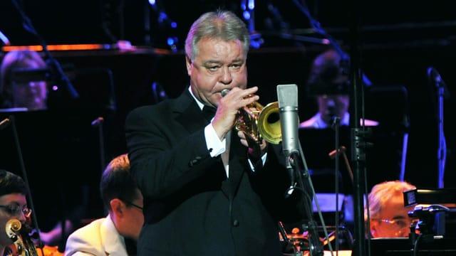 Ein Mann mit grauen Haaren spielt Trompete auf einer Bühne, im Hintergrund ein Orchester.