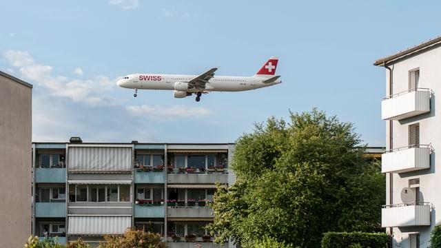 Ein Flugzeug fliegt ganz knapp über ein Mehrfamilienhaus.