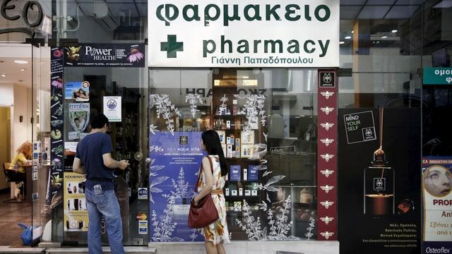 Zwei Touristen stehen vor einer geschlossenen Apotheke in Athen.