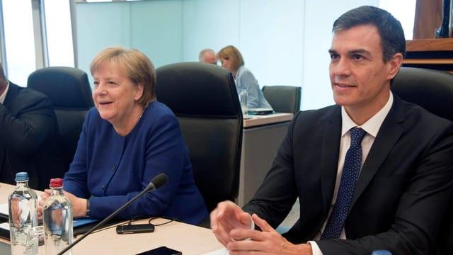 Merkel und Sanchez sitzen an einem Tisch nebeneinander.