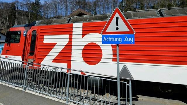 Eine Lokomotive der Zentralbahn hinter einem Verkehrsschild mit dem Aufdruck «Achtung Zug»