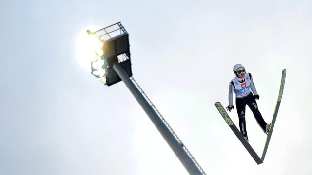 Simon Ammann in der Luft bei einem Schanzensprung.