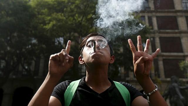 Ein junger Mexikaner raucht und gestikuliert.