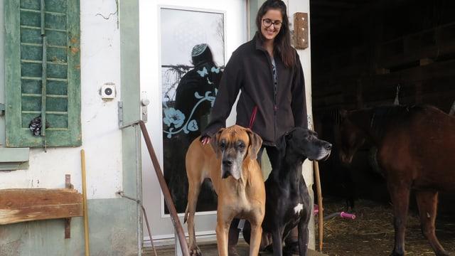 2 Hunde und eine Frau stehen vor einer Haustür