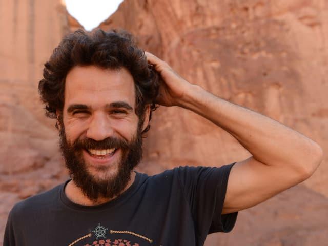 Kutiman steht lachend vor einer Felswand.